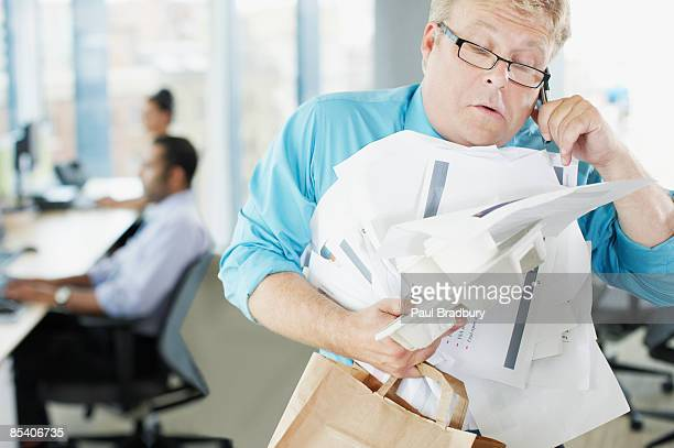 Businessman talking on phone holding paperwork and coffee