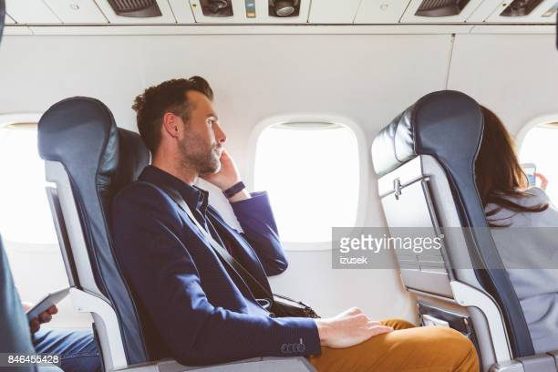 businessman talking on phone in flight - izusek stock pictures, royalty-free photos & images