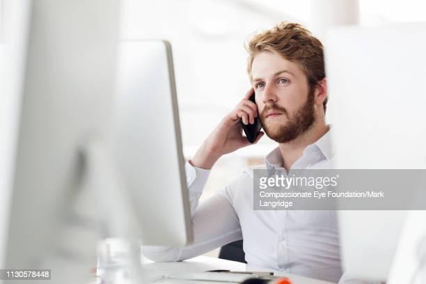 businessman talking on phone in modern office - finanzwirtschaft und industrie stock-fotos und bilder