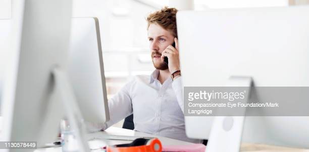 businessman talking on phone in modern office - business finance and industry stock pictures, royalty-free photos & images