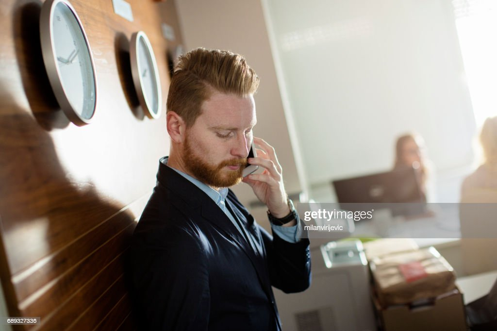 Businessman talking on phone in the office : Stock Photo