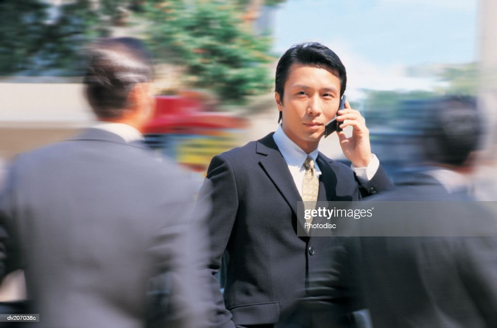Businessman talking on phone, people rushing by : Stock Photo