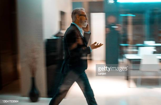 businessman talking on phone while walking - blurred motion stock pictures, royalty-free photos & images