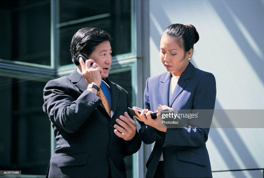Businessman talking on phone, woman checking organizer : Stock Photo