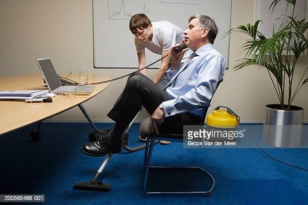 Businessman talking on phone, young man vacuuming carpet