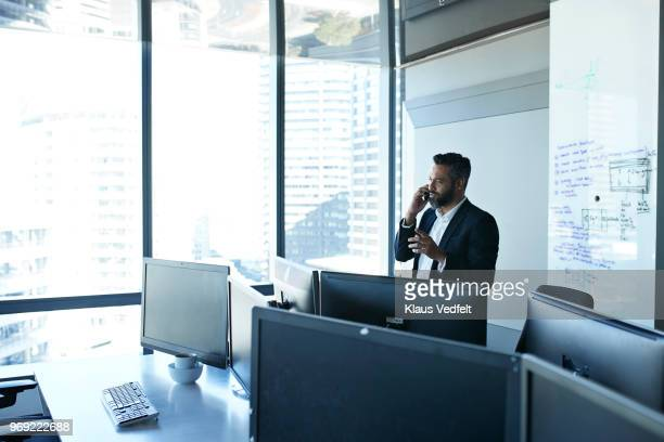 Businessman talking on smartphone inside office