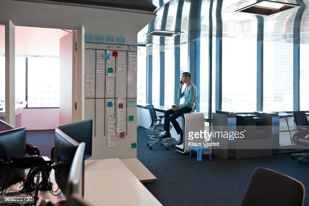 businessman talking on smartphone inside office - solo un uomo foto e immagini stock
