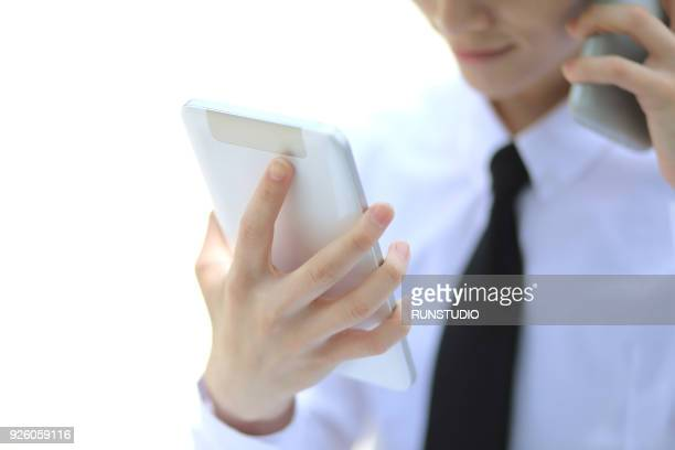 Businessman talking on smartphone with digital tablet outdoors