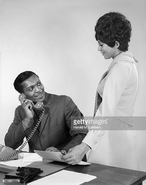 businessman talking on telephone and businesswoman holding document - {{ collectponotification.cta }} fotografías e imágenes de stock