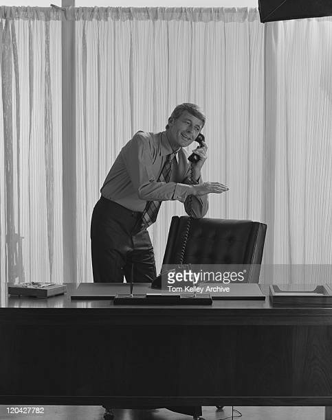 Businessman talking on telephone in office, smiling