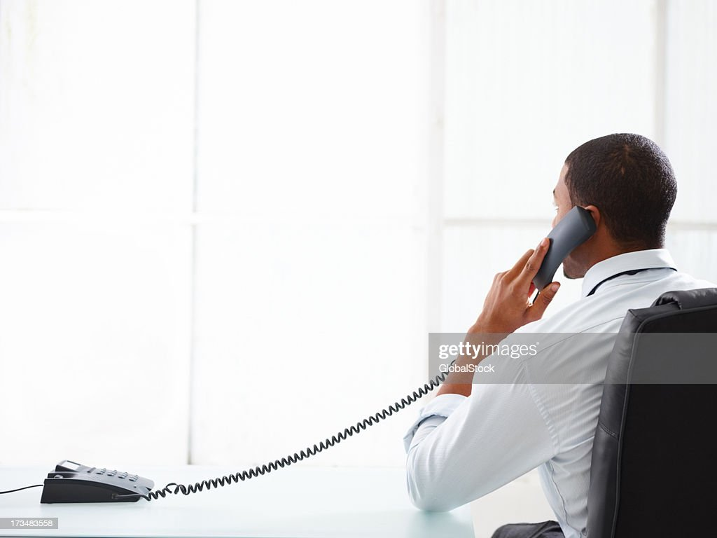Businessman talking on the phone in his office : Stock Photo