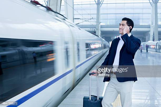 Businessman talking on the phone on the railroad platform by a high speed train in Beijing