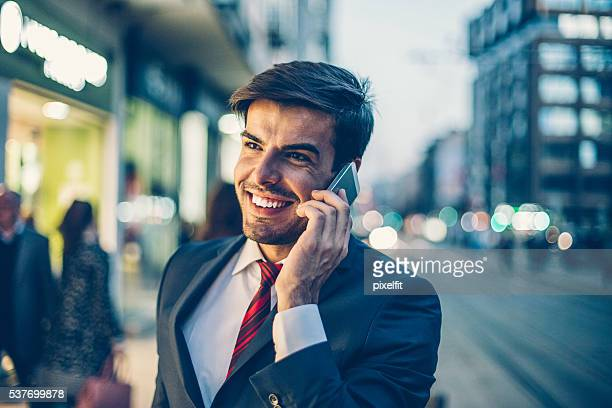 Businessman talking on the phone outdoors in the evening