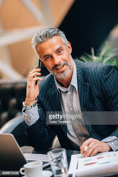 uomo d'affari parla sul telefono  - solo un uomo maturo foto e immagini stock