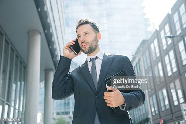 Businessman talking on the phone walking in city