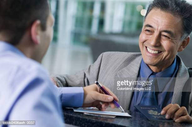 Businessman talking to a young man across an airport counter