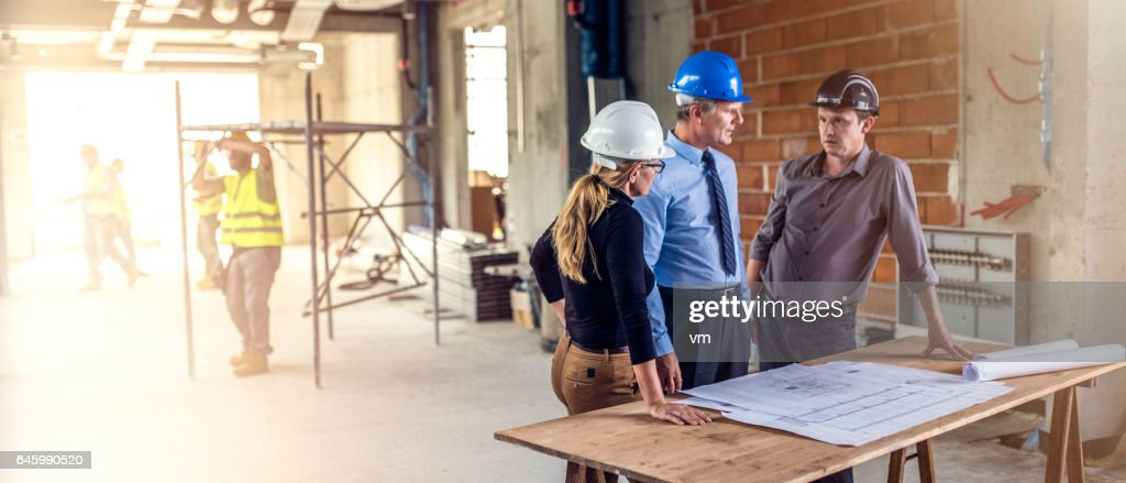 Businessman talking to architects at construction site : Stock Photo