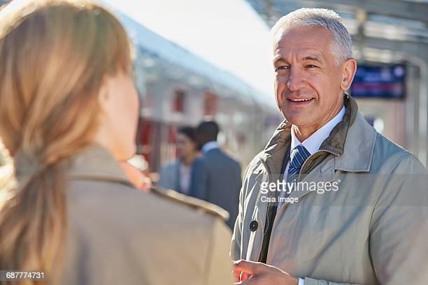 Businessman talking to businesswoman on train station platform