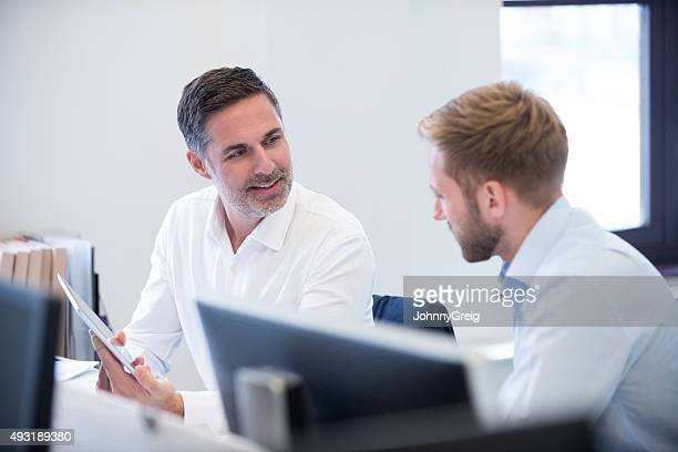 Businessman talking to colleague showing digital tablet