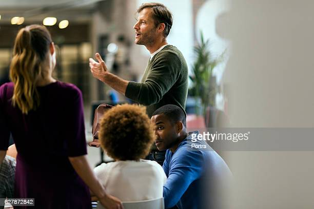 businessman talking to colleagues in meeting - smart casual stock pictures, royalty-free photos & images