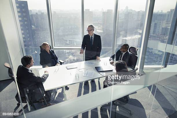 businessman talking to colleagues in meeting - business meeting stock pictures, royalty-free photos & images