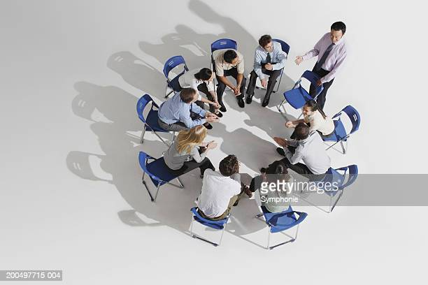 businessman talking to colleagues seated in circle, elevated view - 作戦会議 ストックフォトと画像