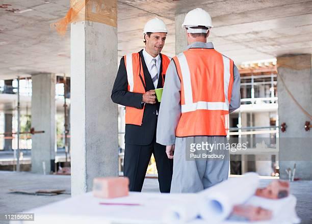 Geschäftsmann Gespräch mit Bau Arbeiter auf der Baustelle