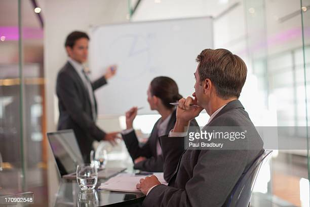 businessman talking to co-workers in conference room - persuasion stock pictures, royalty-free photos & images