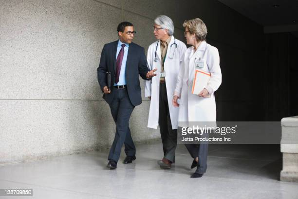 businessman talking to doctors - jetta productions stock pictures, royalty-free photos & images