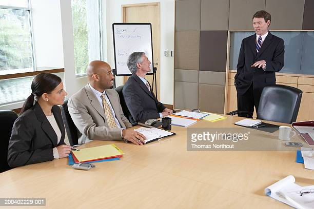 Businessman talking to executives during meeting in boardroom