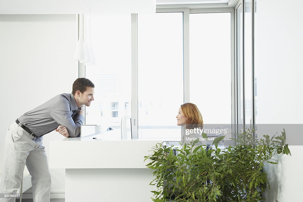 Businessman talking to office receptionist : Stock Photo