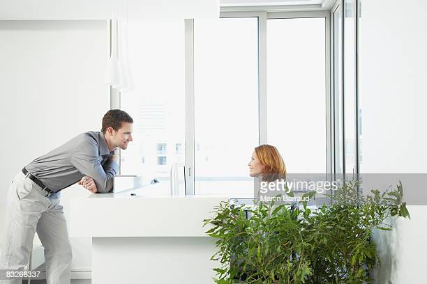 Businessman talking to office receptionist