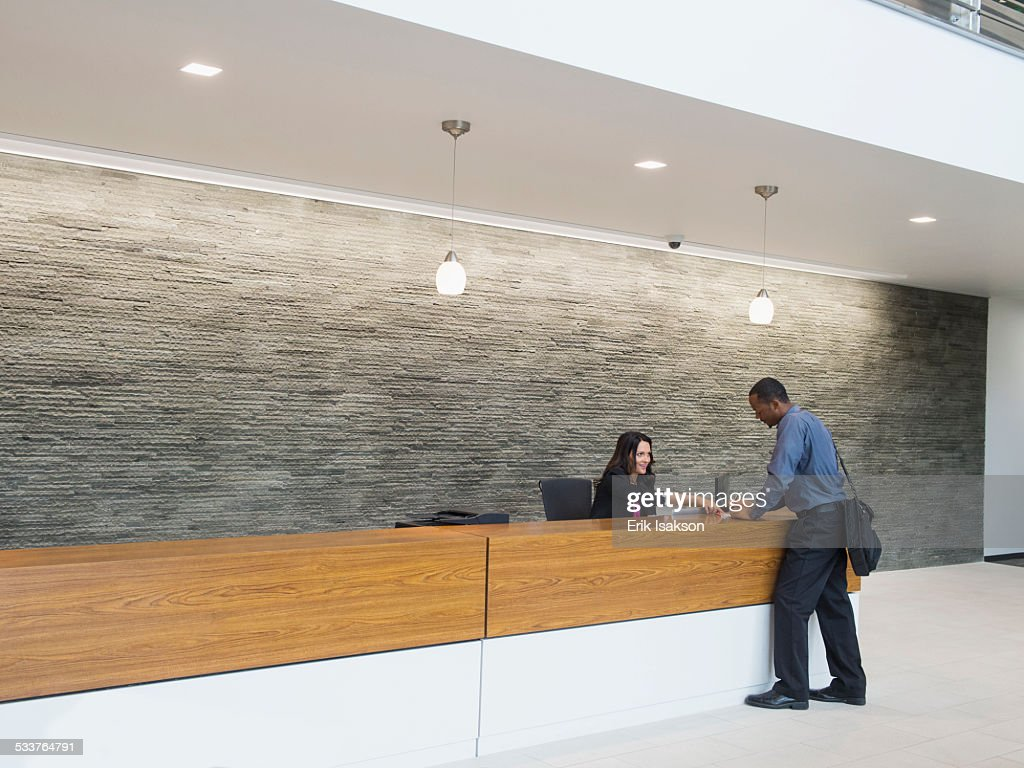 Businessman talking to receptionist at office front desk : Foto stock