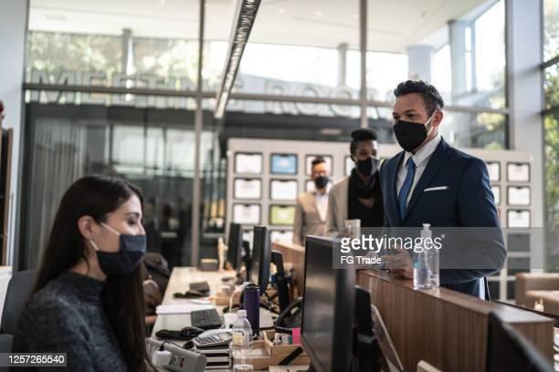 affärsman pratar med receptionist vid ingången till kontorets lobby - med ansiktsmask - opening event bildbanksfoton och bilder