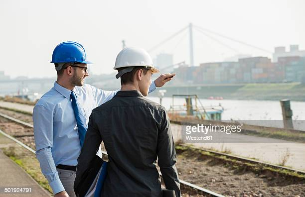 Businessman talking to teenager at container terminal