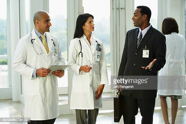 Businessman talking with doctors, smiling