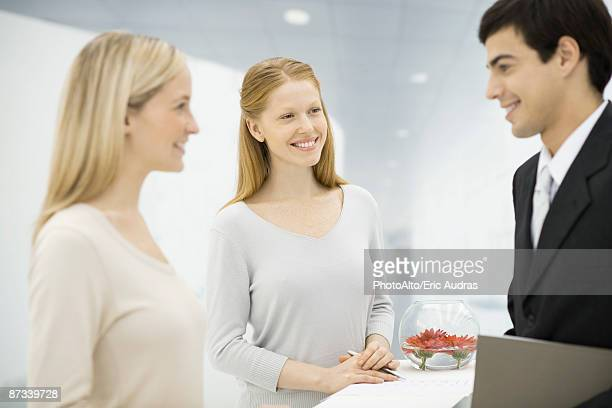 Businessman talking with two receptionists at counter, focus on women in center