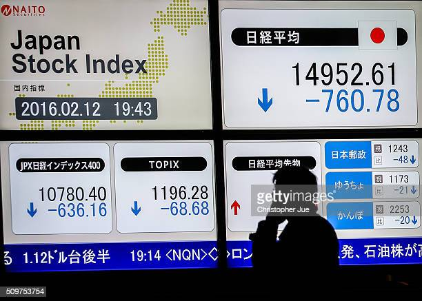 A businessman talks on his mobile phone in front of a stock market indicator board on February 12 2016 in Tokyo Japan The Nikkei Stock Average...