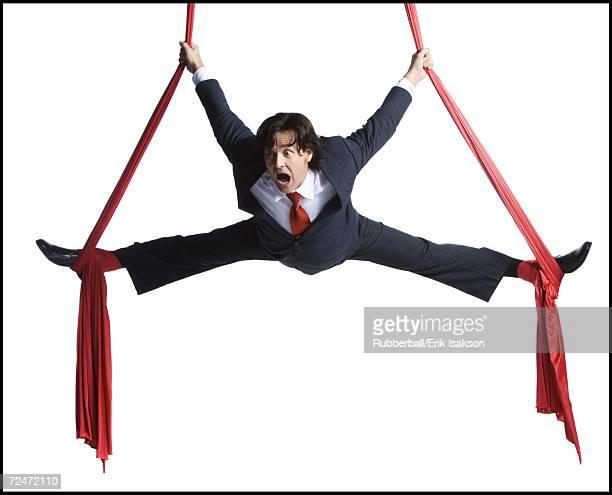 businessman tangled in red drapes - split acrobatiek stockfoto's en -beelden
