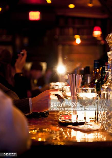 Businessman tapping cigar at bar