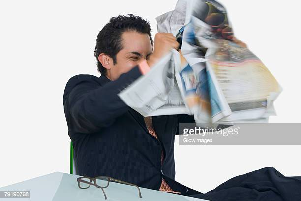 Businessman tearing a newspaper in frustration
