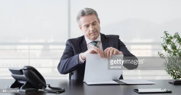 Businessman tearing document