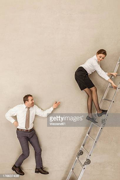 Businessman teasing while businesswoman climbing ladder in office