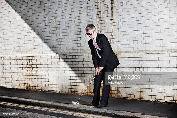 Businessman teeing off on city street