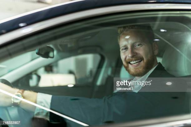 businessman testing car in car dealership - test drive stock pictures, royalty-free photos & images