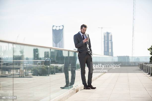 Businessman Text Messaging From Mobile Phone On Patio