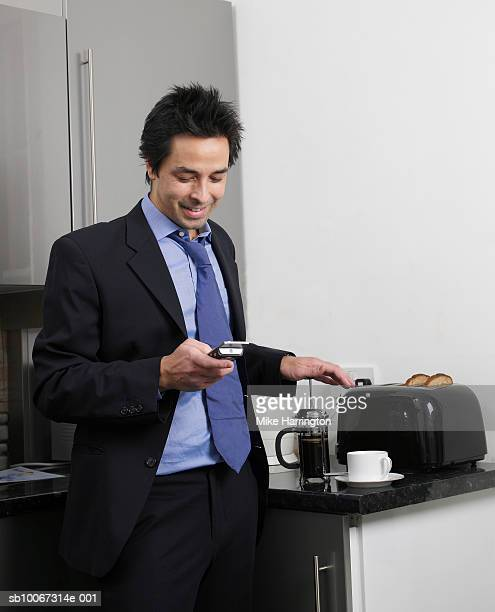 Businessman text messaging in domestic kitchen