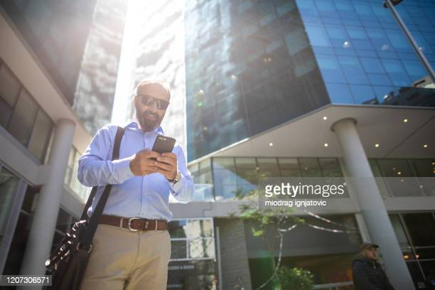businessman text messaging in front of office building - shoulder bag stock pictures, royalty-free photos & images