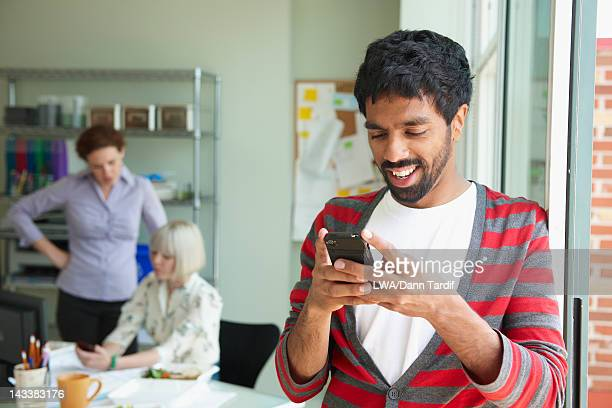 businessman text messaging in office - indian subcontinent ethnicity stock pictures, royalty-free photos & images