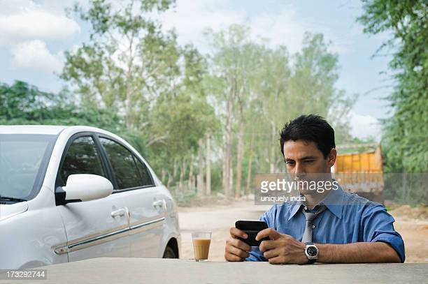 Businessman text messaging on a mobile phone and having tea